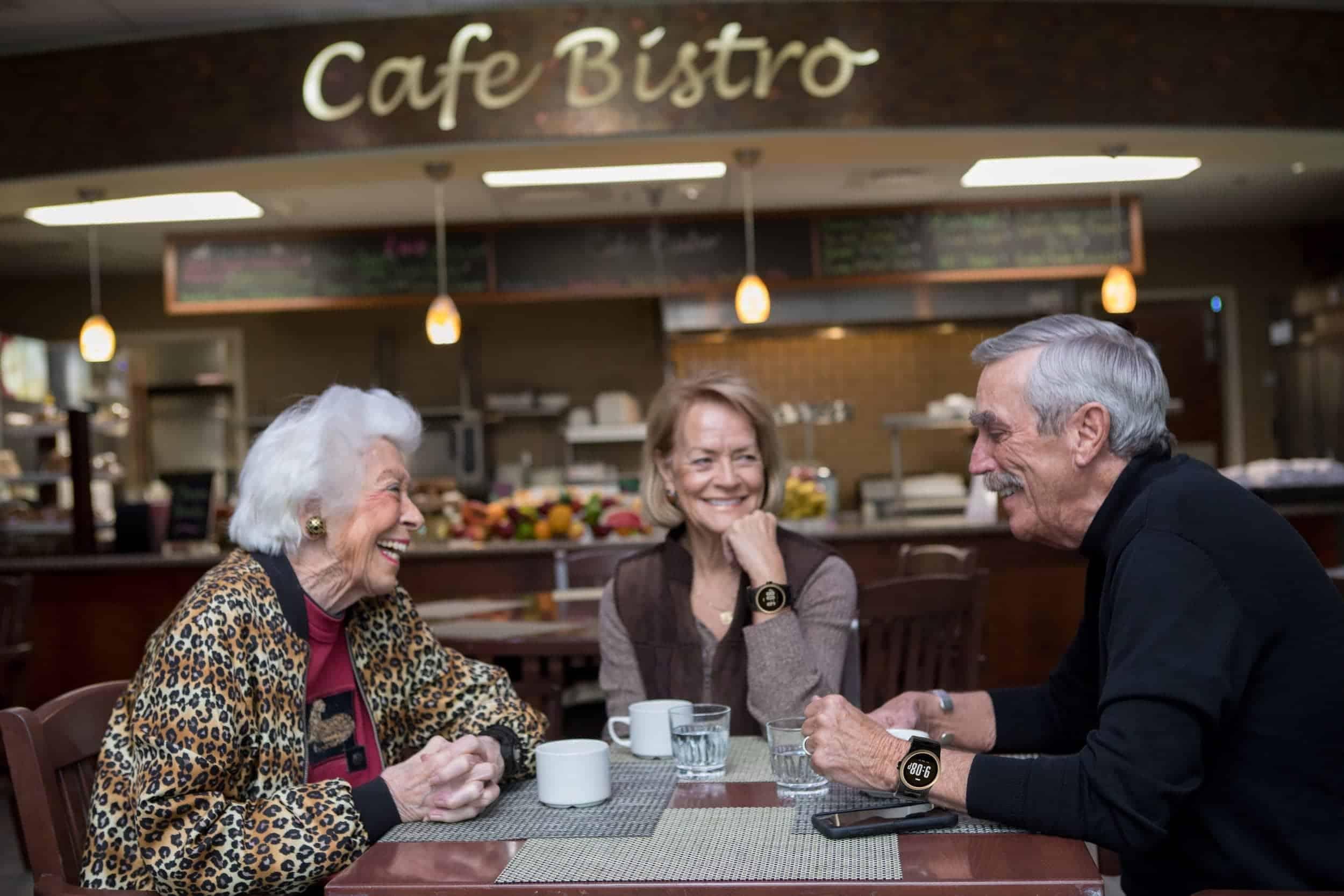 Group sitting in cafe, man wearing kanega watch